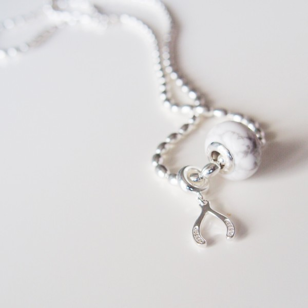 The wishbone and howlite charm on the rice bead necklace.